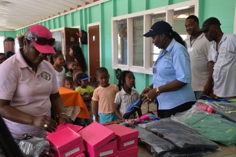 Minister within the Ministry of Communities with responsibility for Housing, Valerie Adams-Patterson-Yearwood handing out school supplies to students of Ituni