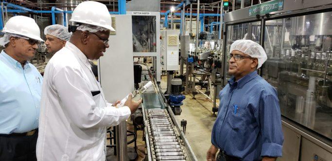 Finance Miniser Winston Jordan examins a bottle during his visit to the DDL Bottling Plant