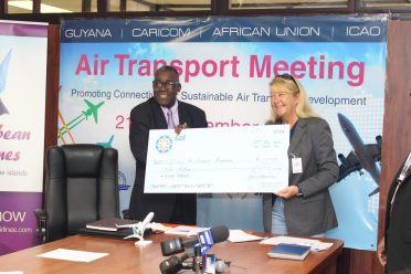 Sol Petroleum's representative, Liz Wyatt hands over a cheque of $1million to the Director of Marketing and Operational Support