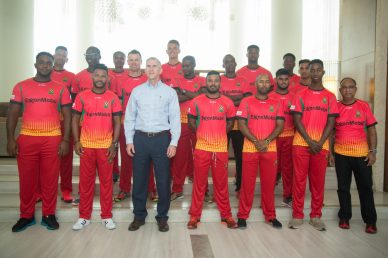 - ExxonMobil's Country Manager, Rod Henson [center] poses with the Guyana Amazon Warriors team