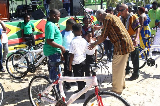 President Granger interacts with some of the beneficiaries of the bicycles which were handed out on Emancipation Day. Also, in the photo is Minister of Social Cohesion, Dr. George Norton