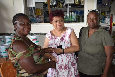 Fire victim Shelly Long receives a receipt for building materials donated by the Ministry of Social Protection and People's National Congress-Reform Region Five official, Carol Nurse [right]