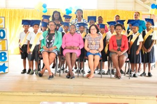 First Lady, Mrs. Sandra Granger (seated second right) and teachers of the Lusignan Primary School take a photo with the graduating class.