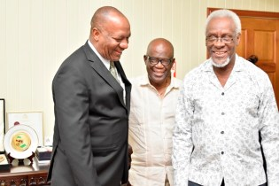 Minister Harmon shares a light moment with Mr. Patterson and Mr. Alston Stewart, Aide to Mr. Patterson.