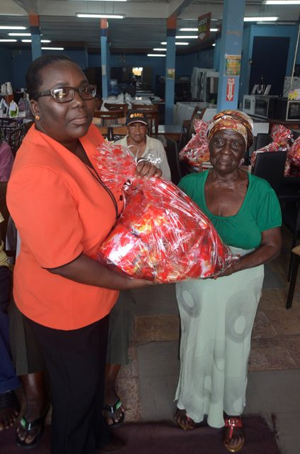 Lucky Dollar Manager, Ineze Murry distributing hamper to 86-years-old Anna Lester.