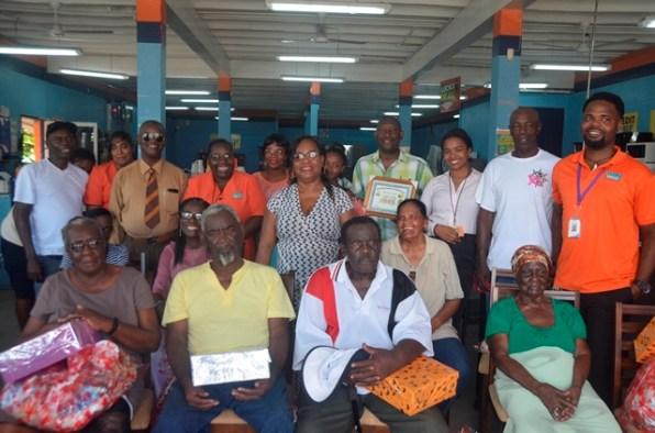 Senior citizens receiving hamper from representatives of the Rose Hall Town Anniversary and Development Organisation (RHTADO).