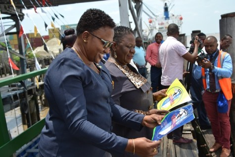 Minister within the Ministry of Public Infrastructure, Annette Ferguson, and Director General of MARAD, Claudette Rogers, examine the new logos certifying the fitness of a vessel to operate.