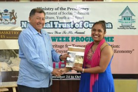 Minister of Indigenous Peoples' Affairs, Sydney Allicock receives first copy of Akawaio Basketry Techniques from Chief Executive Officer (CEO) of the National Trust of Guyana Nirvana Persaud.