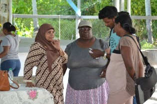 Technical Officer Natasha Singh-Lewis [left] interacting with some of the participants during the sensitisation exercise.