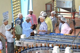Minister of Finance Winston Jordan (centre blue shirt) with Banks DIH Executives at an assembly line for Banks Beer at Thirst Park.