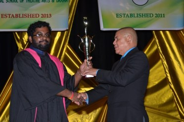 Subraj Singh receiving his award for Best Graduation Student out of the National School of Theatre Arts and Drama from Minister of Social Cohesion, Dr. George Norton.