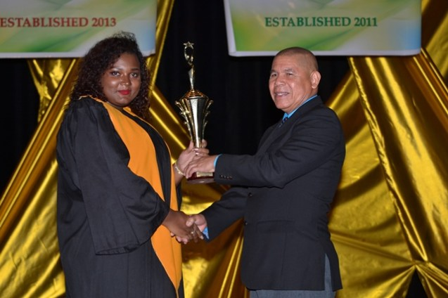 Joanna Suchit receiving her award for Best Graduation Student out of the E.R Burrowes School of Art from Minister of Social Cohesion, Dr. George Norton.