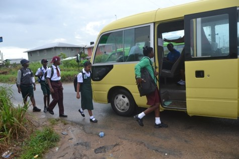 Students entering the David G school bus on their way to school.