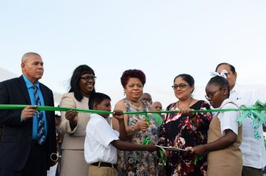 Minister of Social Protection, Anma Ally cuts the ribbon to declare the Region Five Regional Agriculture and Commerce Expo, RACE. She is surrounded by Minister of Social Cohesion, Dr. George Norton [left] Minister within the Ministry of Public Health, Dr. Karen Cummings [second left], Mrs. Sita Nagamootoo [second right], Prime Minister Moses Nagamootoo [right] and school children