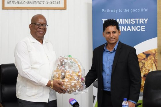 Minister of Finance, Winston Jordan being presented with a basket locally manufactured product by GSMA President Shyam Nokta.