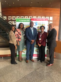 Minister Hughes with Secretary-General of Caribbean Postal Union, Guillermo Raymond, and colleagues