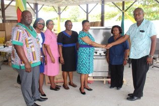 Alex foster, first from right does a formal handshake with minister Volda Lawrence to hand over the items contributed by Food For the Poor.