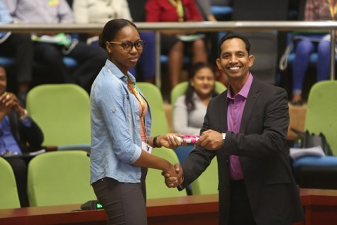 Sahrira Roberts receiving her scholarship from Chief Executive Officer of Cacique Inc., Fazil Bacchus.