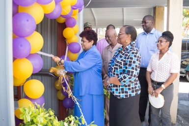 Minister of Social Protection, Amna Ally, Minister within the Ministry of Social Protection, Keith Scott and Permanent Secretary of the ministry, Lorraine Baird during the symbolic cutting of the ribbon to commission the lifts at the Palms Geriatric Home.