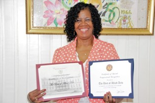 Ms. Lorraine Barker-King displaying certificates of recognition as a result of the Award being conferred on the Unit of Allied Arts