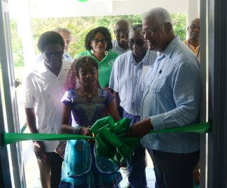 Minister Holder, Mr. Fredrick Flatts and other officials while cutting the ribbon to officially commission the building.