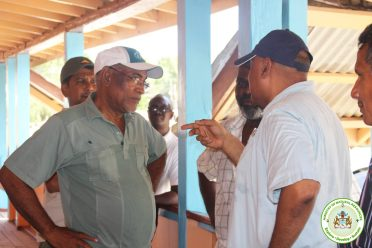 Minister Trotman speaks with Hector Mendonca and Leroy Saul