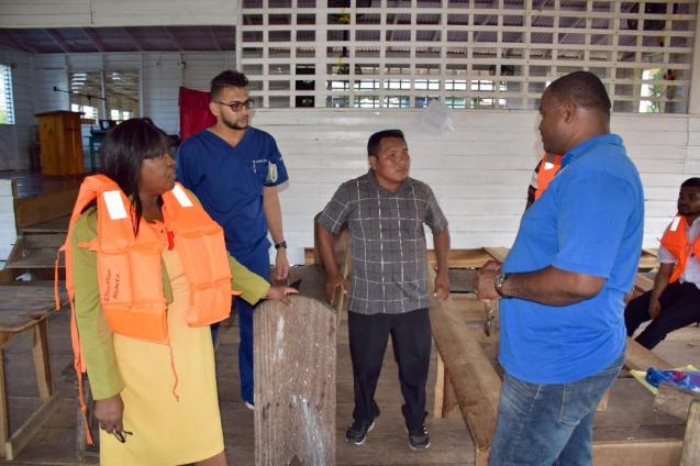 Sherman Lewis, Chairperson, Community Development Council, Smyth's Creek, Region One (at Centre) in discussion with Minister within the Ministry of Public Health, Dr. Karen Cummings and others