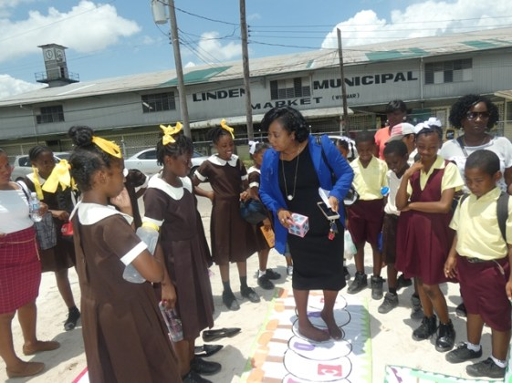 Teacher engaging some students of the Regma Primary School in a mathematical game.