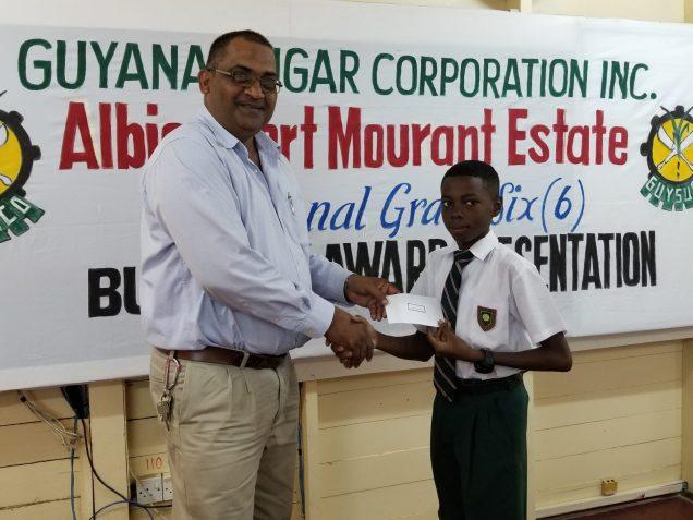 Manager of Albion Estate, Threbhowan Shiwprasad presenting bursary award to Joshua Thomas