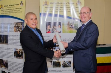 Minister of Social Cohesion, Dr. George Norton [left] receiving a copy of the Map of Fort Nassau from Head of the Digitization Department of the National Archives of the Netherlands Arjan Agema.