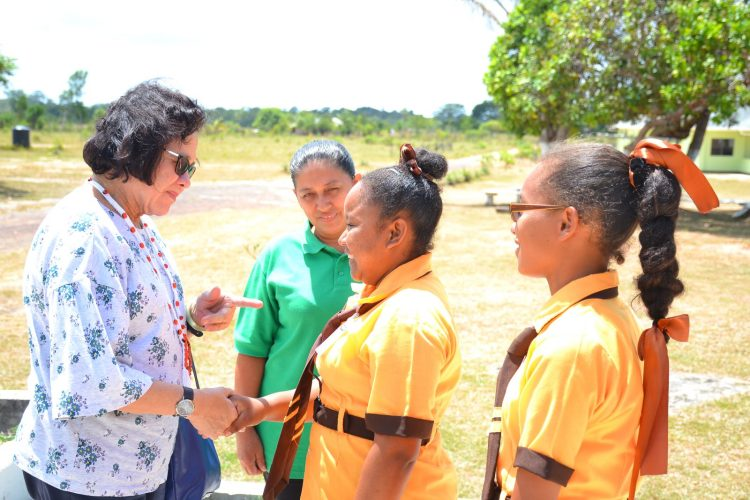 First Lady, Mrs. Sandra Granger greets two students of the Annai Secondary School