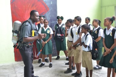 Officers of the Guyana Fire Service (GFS) demonstrating fire prevention techniques to the students.