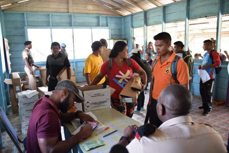 Members of the Guyana Police Force (GPF) complete licence registration during the handing over of firearms to residents from indigenous communities in Region Seven