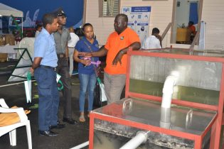 A Ministry of Communities representative explaining the importance of properly constructed septic tanks to patrons