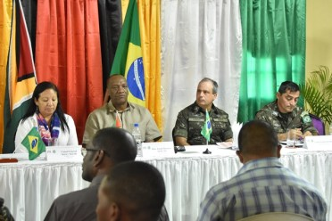 Consul-General of Guyana to Boa Vista, Brazil, Ms. Shirley Melville (right) and Minister of State, Mr. Joseph Harmon (second right) sit with members of the Brazilian Army's 6th Battalion Engineering Corps at the simple welcome ceremony which marks the beginning of the well drilling project.