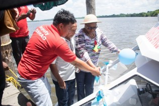 Minister of Public Health, Volda Lawrence and Deputy Toshao, Henry Herman cut the ribbon to commission the River Ambulance in the presence of a religious leader of the village.