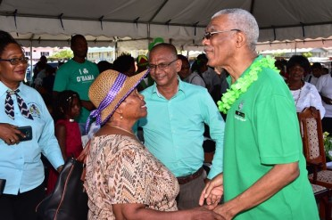 President David Granger greets an elderly woman at the conclusion of a community meeting held at the Anna Regina car park today.