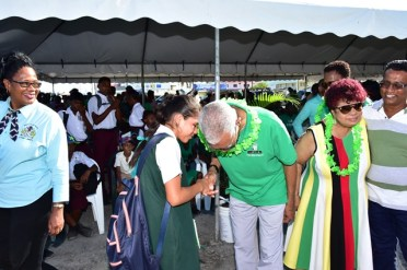 President David Granger greets and listens keenly to a school aged girl who was keen to meet him.