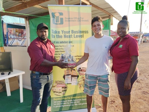 Staff of GO-Invest, Samora Watkins (left) and Jeanne Mitchell (right) hands over a hamper to a winning participant, Brazilian Bryan Joseph.