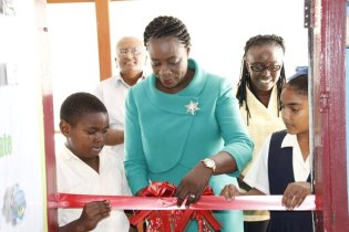 Minister Henry and students of Tucville Primary School performing the ceremonial cutting of the ribbon to officially commission the IT Lab.