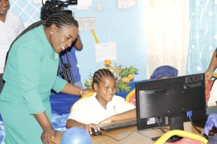 A student operating one of the computers in the Eccles Primary School IT lab as Minister Henry looks on.