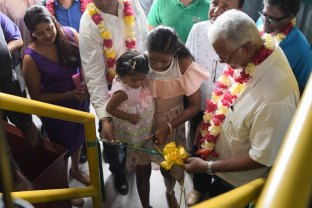Minister of Agriculture, Noel Holder and a young resident cutting the ribbon at the commissioning of the pump.