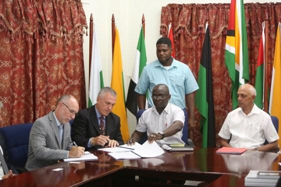 President of Axilogic, Michael Chettleburgh, Permanent Secretary at the Ministry of Communities, Emile Mc Garrell and Representative of MPAC, Antoni Wisniowski signing the contract.