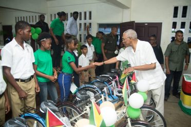 President Granger handing over a bicycle to a young lady