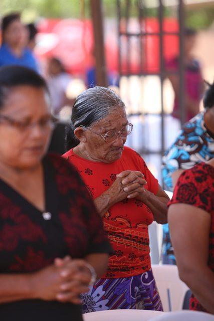 Elderly woman prays at interfaith service.