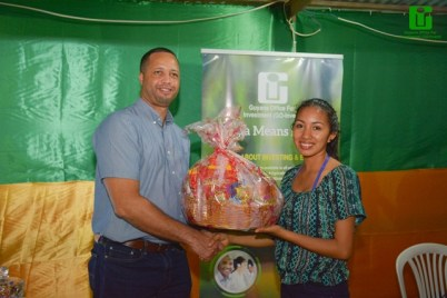 GO-Invest's CEO, Mr. Owen Verwey presents Lethem resident Fiolene Jacobs with her hamper from, following her successful participation in the Quiz on investment at GO-Invest's booth during the Lethem Town Week launch.