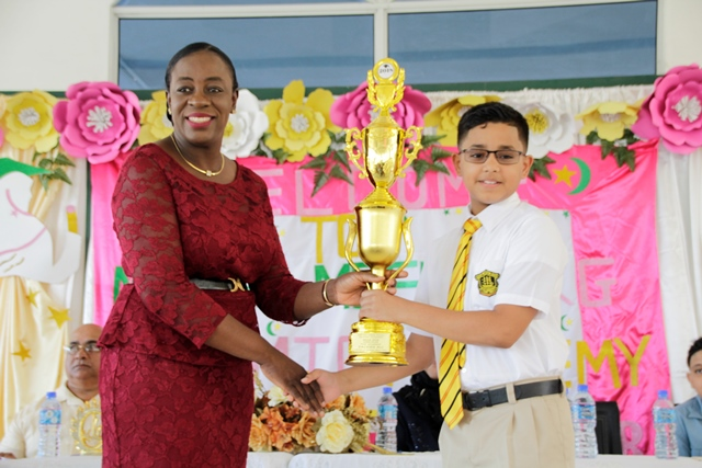 Minister of Education, Hon. Nicolette Henry presenting top NGSA Student, Zackiea Ali with his trophy.
