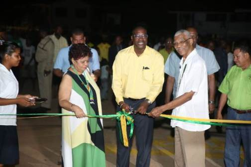 Minister of Public Infrastructure, David Patterson cuts the ribbon to commission Mahdia's internal roads. On the left is Minister of Social Protection, Amna Ally and on the right is His Excellency President David Granger.