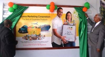 Minister Holder and GMC Board Chairman Omadatt Chandan unveiling the billboard.
