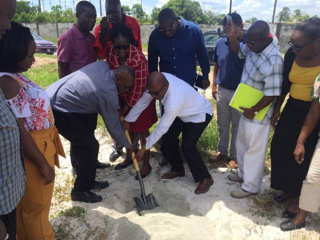 Regional Chairman Renis Morian, Minister within the Ministry of Communities, with responsibility for housing, Valarie Adams-Patterson-Yearwood and National Director of CDC, Eugene Gilbert turning the sod for the new CDC building while other regional and local officials look on.